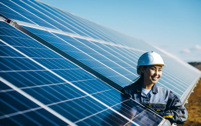 woman standing between solar panels wearing a hard hat